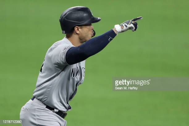 Giancarlo Stanton of the New York Yankees celebrates a grand slam hit against John Curtiss of the Tampa Bay Rays during the ninth inning in Game One...