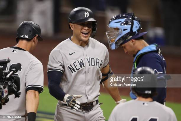 Giancarlo Stanton of the New York Yankees celebrates a grand slam home run as Michael Perez of the Tampa Bay Rays hangs his head during the ninth...