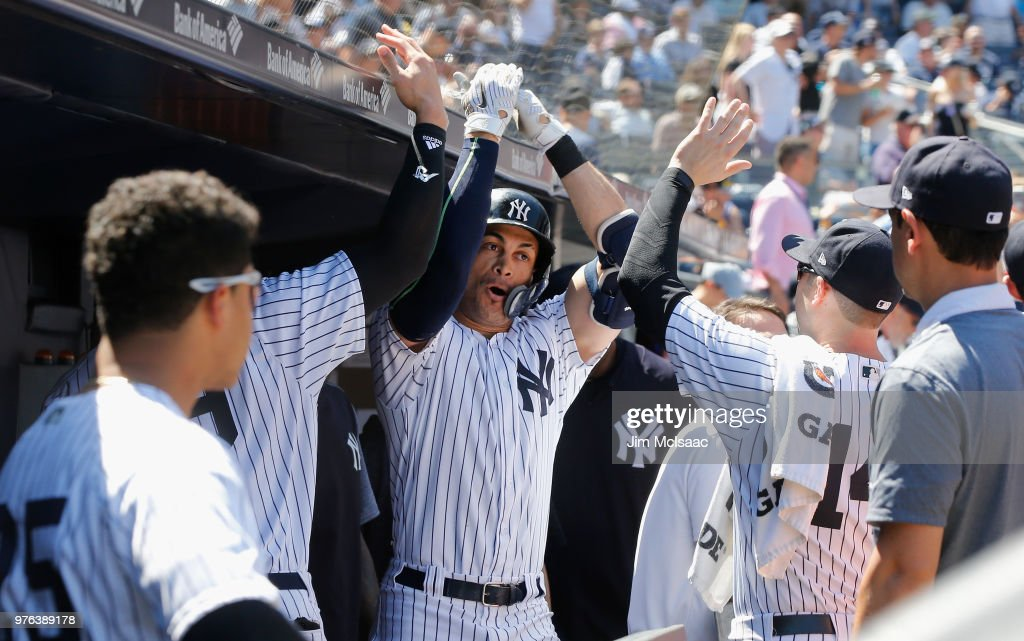 Giancarlo Stanton #27 of the New York Yankees celebrates his fifth inning home run against the Tampa Bay Rays with his teammates in the dugout at Yankee Stadium on June 16, 2018 in the Bronx borough of New York City.