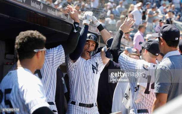 Giancarlo Stanton of the New York Yankees celebrates his fifth inning home run against the Tampa Bay Rays with his teammates in the dugout at Yankee...