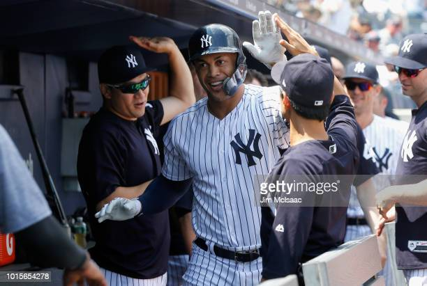 Giancarlo Stanton of the New York Yankees celebrates his first inning home run against the Texas Rangers with his teammates in the dugout at Yankee...