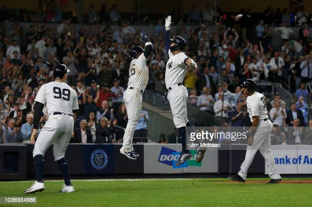 Giancarlo Stanton of the New York Yankees celebrates his fourth inning grand slam home run against the Boston Red Sox with teammates Aaron Judge...