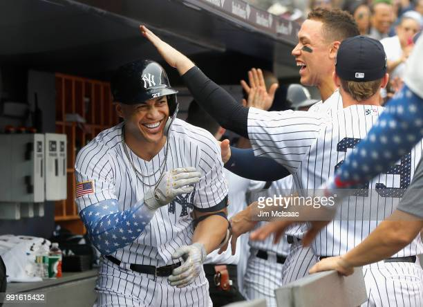 Giancarlo Stanton of the New York Yankees celebrates his third inning threerun home run against the Atlanta Braves with his teammates in the dugout...