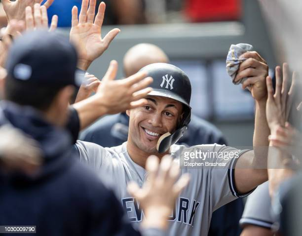Giancarlo Stanton of the New York Yankees celebrates in the dugout after scoring a run on a double by Miguel Andujar of the New York Yankees off of...