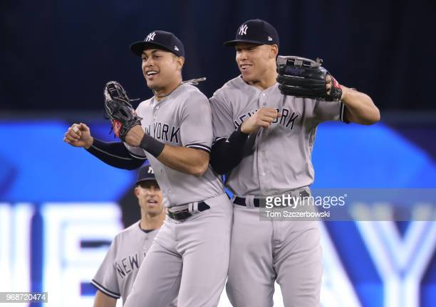 Giancarlo Stanton of the New York Yankees celebrates their victory with Aaron Judge during MLB game action against the Toronto Blue Jays at Rogers...