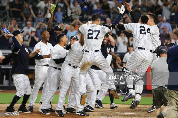 Giancarlo Stanton of the New York Yankees celebrates with his teammates after hitting a tworun walk off home run during the game against the Seattle...