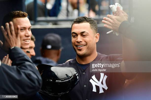 Giancarlo Stanton of the New York Yankees celebrates with teammates after scoring on a double hit by Gary Sanchez during the third inning against the...