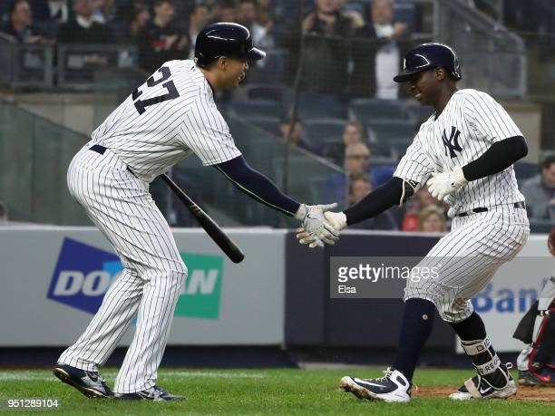 Giancarlo Stanton of the New York Yankees congratulates Didi Gregorius after he hit a solo home run in the third inning against the Minnesota Twins...