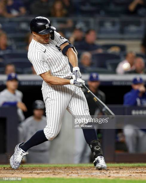 Giancarlo Stanton of the New York Yankees connects on a third inning run scoring sacrifice fly against the Texas Rangers at Yankee Stadium on...