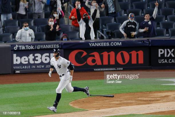 Giancarlo Stanton of the New York Yankees drops his bat as the crowd reacts to his grand slam hit during the fifth inning against the Baltimore...