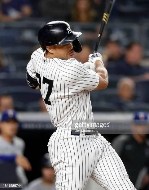 Giancarlo Stanton of the New York Yankees follows through on a third inning run scoring sacrifice fly against the Texas Rangers at Yankee Stadium on...