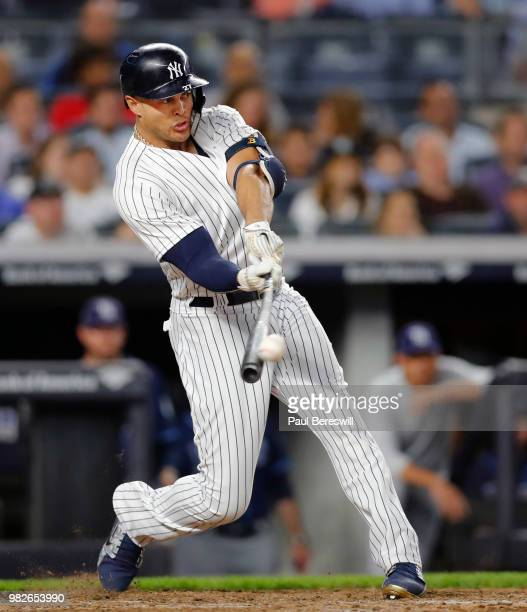 Giancarlo Stanton of the New York Yankees hits a long sacrifice fly to centerfield that scored a run in an MLB baseball game against the Tampa Bay...