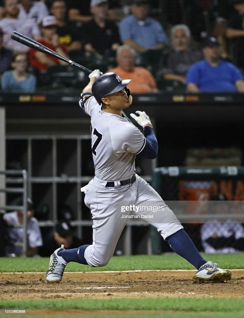 Giancarlo Stanton #27 of the New York Yankees hits a two run home run in the 10th inning against the Chicago White Sox at Guaranteed Rate Field on August 7, 2018 in Chicago, Illinois.