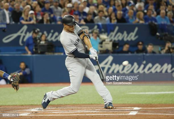 Giancarlo Stanton of the New York Yankees hits a tworun home run in the first inning on Opening Day during MLB game action against the Toronto Blue...