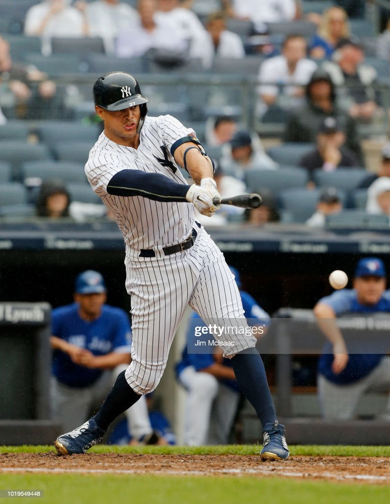 Giancarlo Stanton #27 of the New York Yankees hits an RBI single in the sixth inning against the Toronto Blue Jays at Yankee Stadium on August 19, 2018 in the Bronx borough of New York City.