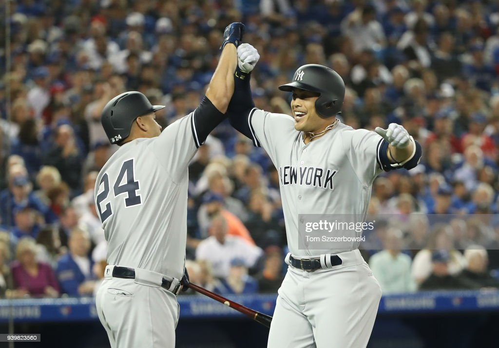Giancarlo Stanton #27 of the New York Yankees is congratulated by Gary Sanchez #24 after hitting a two-run home run in the first inning on Opening Day during MLB game action against the Toronto Blue Jays at Rogers Centre on March 29, 2018 in Toronto, Canada.
