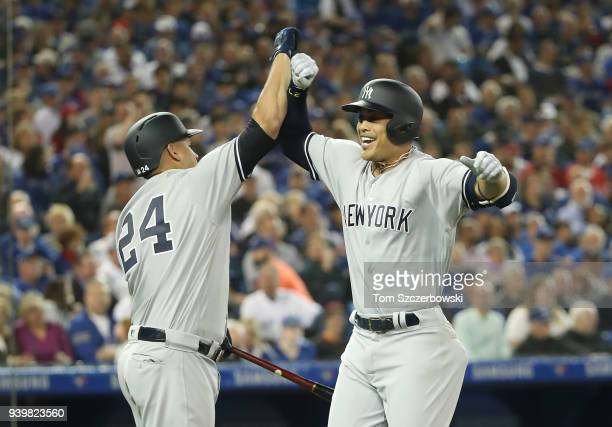 Giancarlo Stanton of the New York Yankees is congratulated by Gary Sanchez after hitting a tworun home run in the first inning on Opening Day during...
