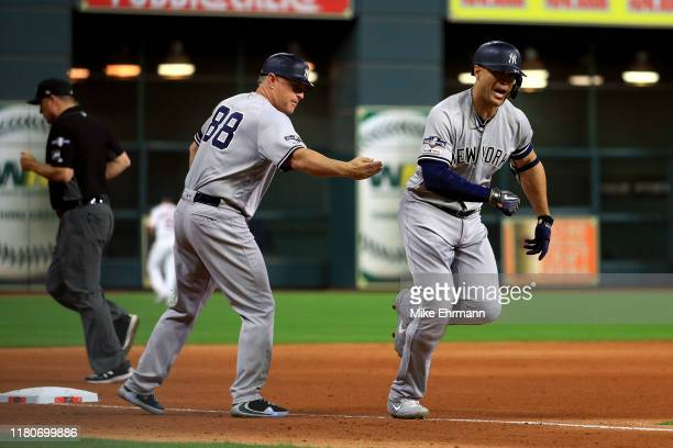 Giancarlo Stanton of the New York Yankees is congratulated by his third base coach Phil Nevin after his solo home run against the Houston Astros...