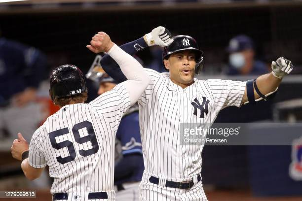 Giancarlo Stanton of the New York Yankees is congratulated by Luke Voit after hitting a two run home run against the Tampa Bay Rays during the eighth...