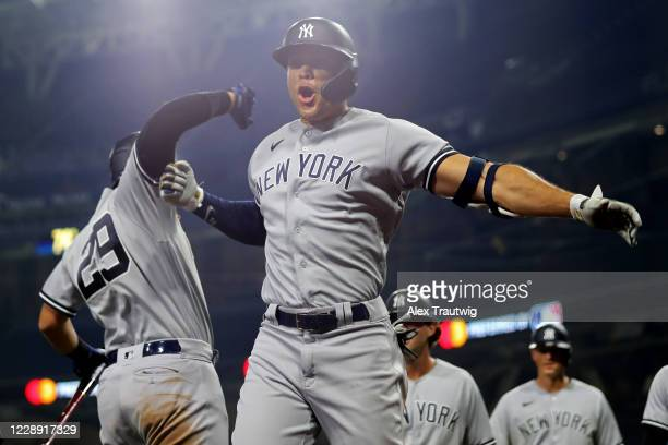 Giancarlo Stanton of the New York Yankees is greeted by teammate Gio Urshela after hitting a grand slam in the ninth inning during Game 1 of the ALDS...
