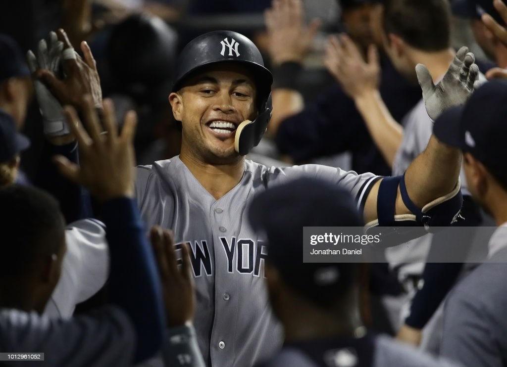 Giancarlo Stanton #27 of the New York Yankees is greeted in the dougout after hitting a two run home run in the 10th inning against the Chicago White Sox at Guaranteed Rate Field on August 7, 2018 in Chicago, Illinois.