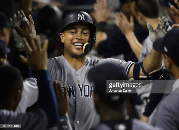 Giancarlo Stanton of the New York Yankees is greeted in the dougout after hitting a two run home run in the 10th inning against the Chicago White Sox...