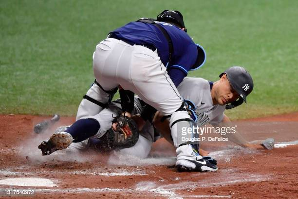 Giancarlo Stanton of the New York Yankees is tagged out by Mike Zunino of the Tampa Bay Rays during the eighth inning at Tropicana Field on May 11,...