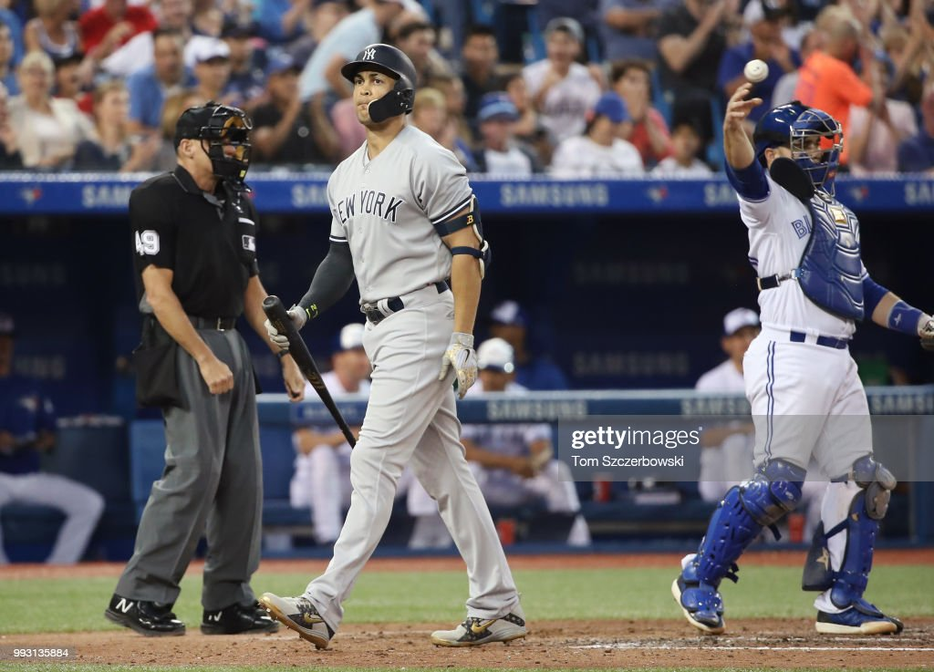 Giancarlo Stanton #27 of the New York Yankees reacts after being called out on strikes with the bases loaded in the fifth inning during MLB game action against the Toronto Blue Jays at Rogers Centre on July 6, 2018 in Toronto, Canada.