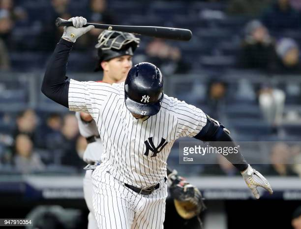 Giancarlo Stanton of the New York Yankees reacts after he hit a pop fly in the third inning as JT Realmuto of the Miami Marlins defends at Yankee...