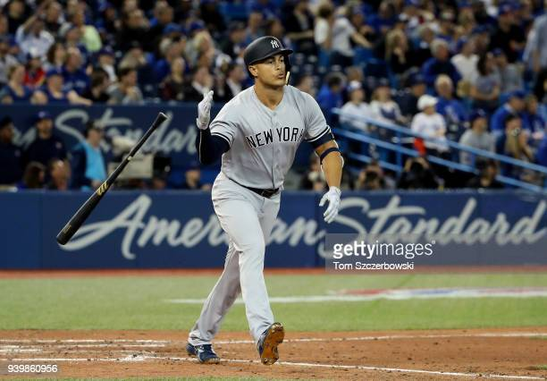 Giancarlo Stanton of the New York Yankees reacts as he hits a solo home run in the ninth inning on Opening Day during MLB game action against the...