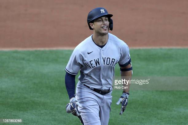 Giancarlo Stanton of the New York Yankees rounds the bases after hitting a two run home run to center field against Max Scherzer of the Washington...