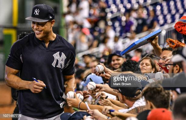 Giancarlo Stanton of the New York Yankees signs autographs for fans before the game against the Miami Marlins at Marlins Park on August 22, 2018 in...
