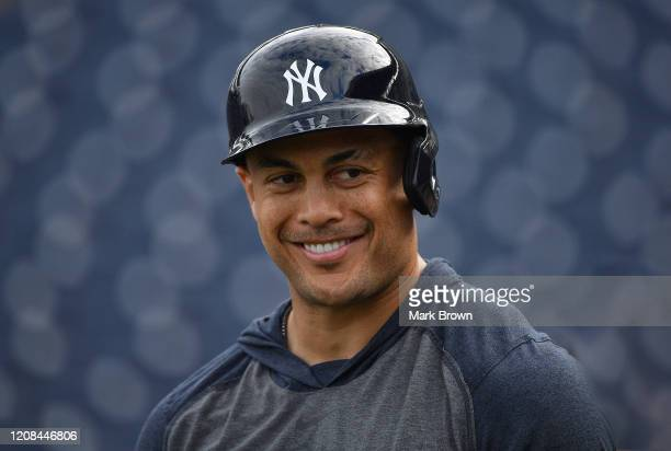 Giancarlo Stanton of the New York Yankees smiling with teammates during batting practice prior to the spring training game against the Pittsburgh...