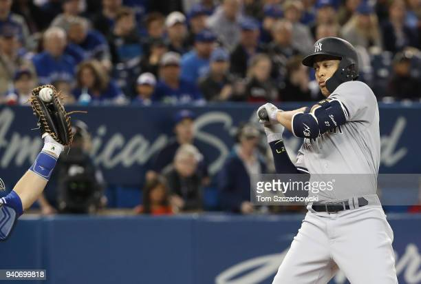 Giancarlo Stanton of the New York Yankees turns away from an inside pitch as he watches it into the glove of Russell Martin of the Toronto Blue Jays...