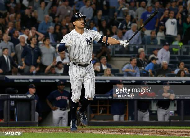 Giancarlo Stanton of the New York Yankees watches the flight of his fourth inning grand slam home run against the Boston Red Sox at Yankee Stadium on...