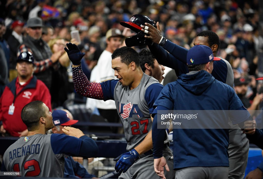 Giancarlo Stanton #27 of the United States, center, is congratulated in the dugout by after hitting a two run home run during the fourth inning of the World Baseball Classic Pool F Game Six between the United States and the Dominican Republic at PETCO Park on March 18, 2017 in San Diego, California.