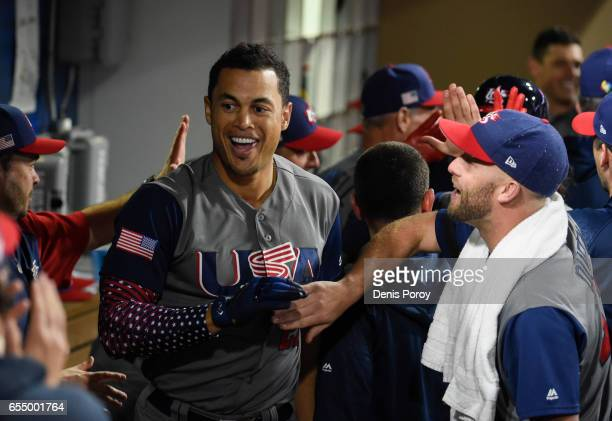 Giancarlo Stanton of the United States left is congratulated in the dugout by after hitting a two run home run during the fourth inning of the World...