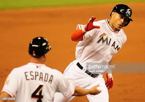 Giancarlo Stanton shacks hands with third base coach Joe Espada after hitting a home run against the Philadelphia Phillies at Marlins Park on...