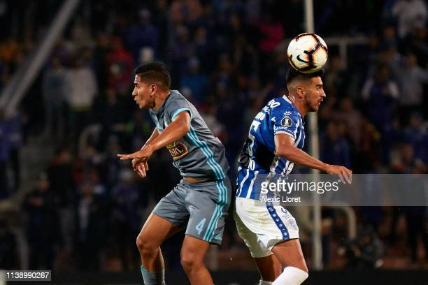 Gianfranco Chávez of Sporting Cristal heads for the ball with Juan Martín Lucero of Godoy Cruz during a group C match between Godoy Cruz and Club...