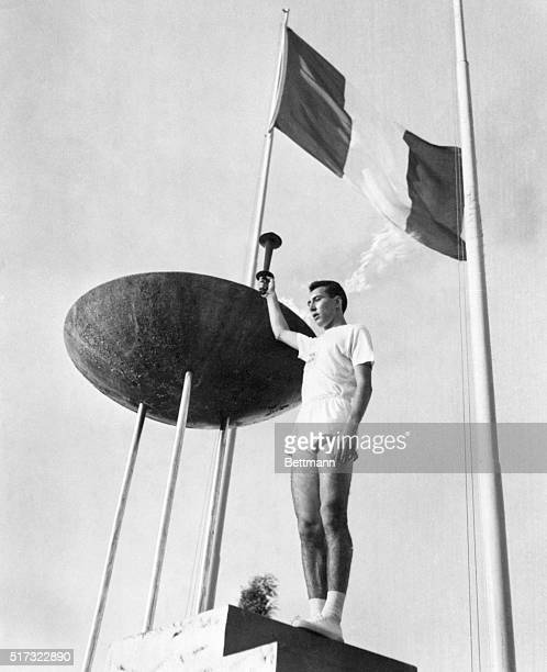 Gianfranco Peris holds up the Olympic torch after lighting the brazier in the opening ceremonies of the 1960 Summer Games.