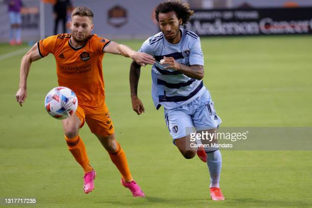 Gianluca Busio of Sporting Kansas City chases for the ball alongside Adam Lundqvist of Houston Dynamo during the first half at BBVA Stadium on May...