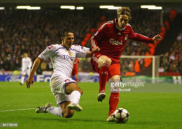 Gianluca Comotto of Fiorentina challenges Fernando Torres of Liverpool during the UEFA Champions League Group E match between Liverpool and...