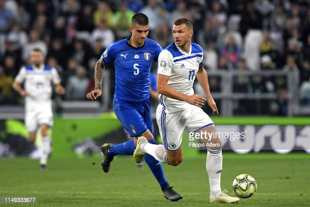 Gianluca Mancini of Italy competes for the ball with Edin Dzeko of Bosnia during the UEFA Euro 2020 Qualifier between Italy and Bosnia and...