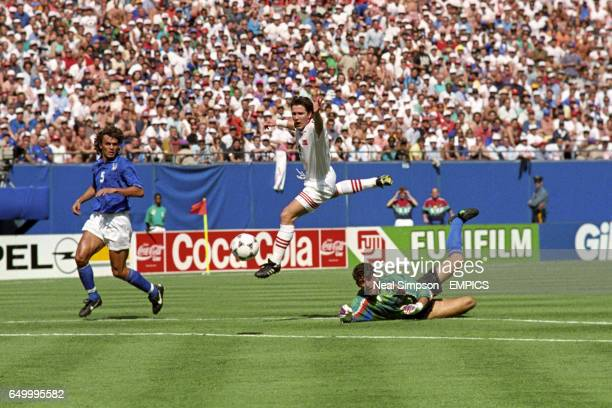 Gianluca Pagliuca, Italy, handles the ball outside the area and is sent off, while Oyvind Leonhardsen, Norway, leaps over