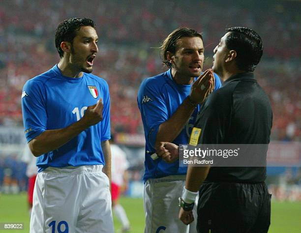 Gianluca Zambrotta and Cristiano Zanetti of Italy protest to referee Byron Moreno of Ecuador after he awarded a penalty to South Korea during the...