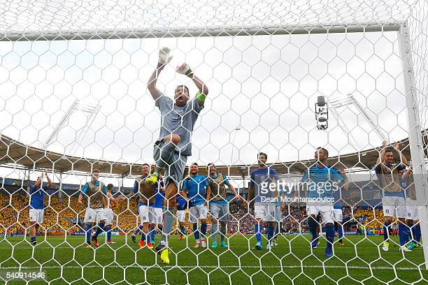 Gianluigi Buffon of Italy jumps to the crossbar as the Italian team celebrate victory in the UEFA EURO 2016 Group E match between Italy and Sweden at...