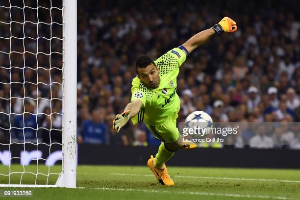 Gianluigi Buffon of Juventus dives but fails to stop Casemiro of Real Madrid shot from going in for Real Madrid second goal during the UEFA Champions...