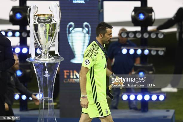 Gianluigi Buffon of Juventus Turin walks past The Champions League trophy after the UEFA Champions League Final between Juventus and Real Madrid at...