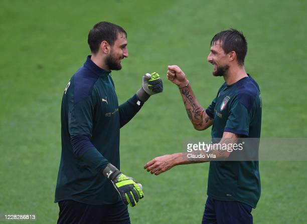 Gianluigi Donnarumma and Francesco Acerbi of Italy react during a training session at Centro Tecnico Federale di Coverciano on August 31, 2020 in...