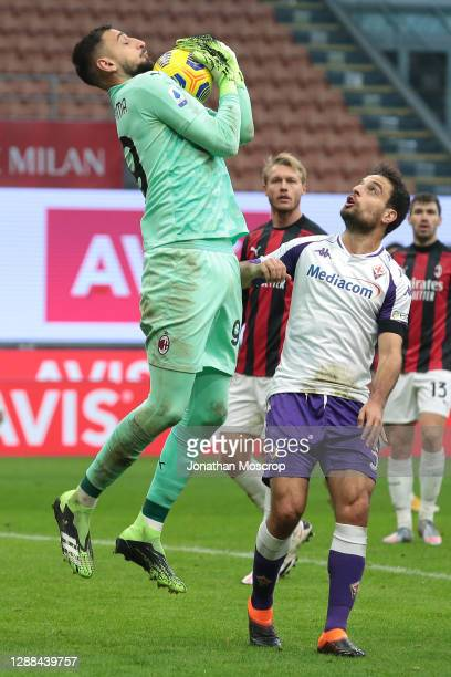 Gianluigi Donnarumma of AC Milan gathers the ball under pressure from former team mate Giacomo Bonaventura of ACF Fiorentina during the Serie A match...